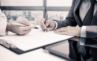 Avocat signant un document avec son client